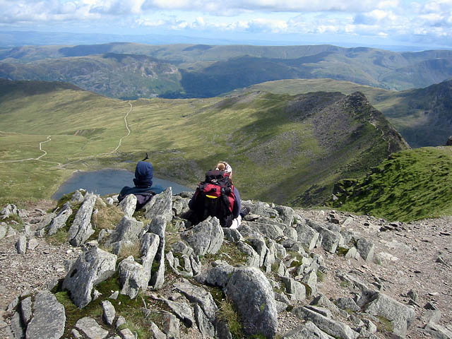 Walkers look down on Striding Edge from the summit of Helvellyn