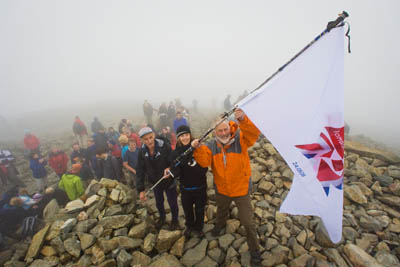 Sir Chris raises the Olympic flag, with Jos Naylor and Laura Park, on the summit of Scafell Pike