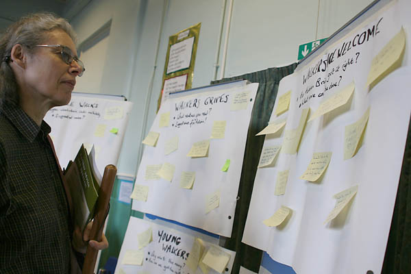A visitor looks a Post-It Notes on the boards at the event