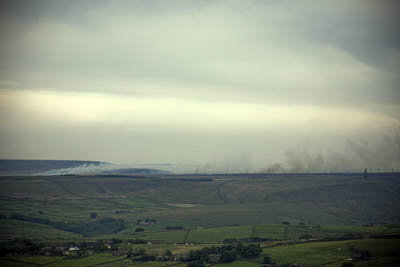 Smoke from the moor fires drifts across the Pennine landscape