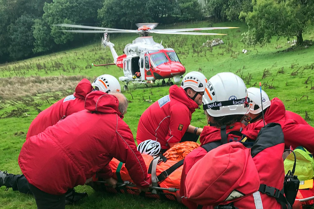 Rescuers with the injured cyclist and the Coastguard helicopter. Photo: Aberdyfi SRT