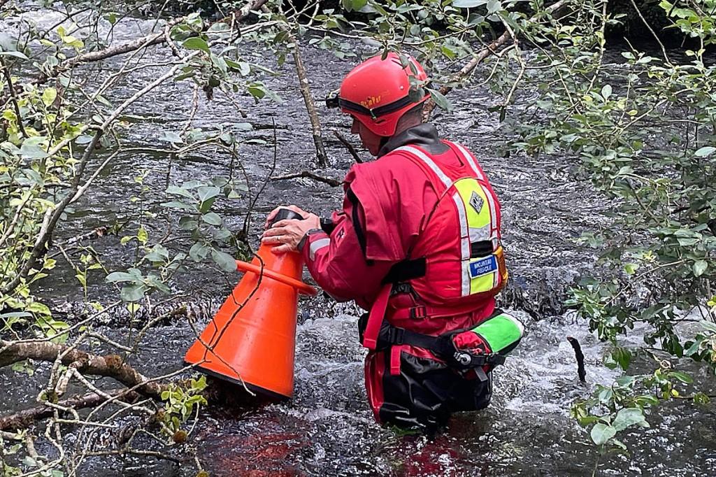 An Aberdyfi team member searches water debris near Llanidloes. Photo: Aberdyfi SRT