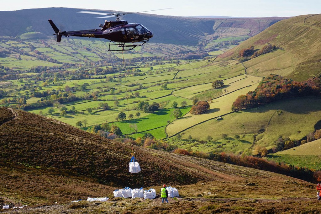A helicopter airlifts stone on to the Ringing Roger path on Kinder Scout as part of last year's campaign. Photo: Adam Long