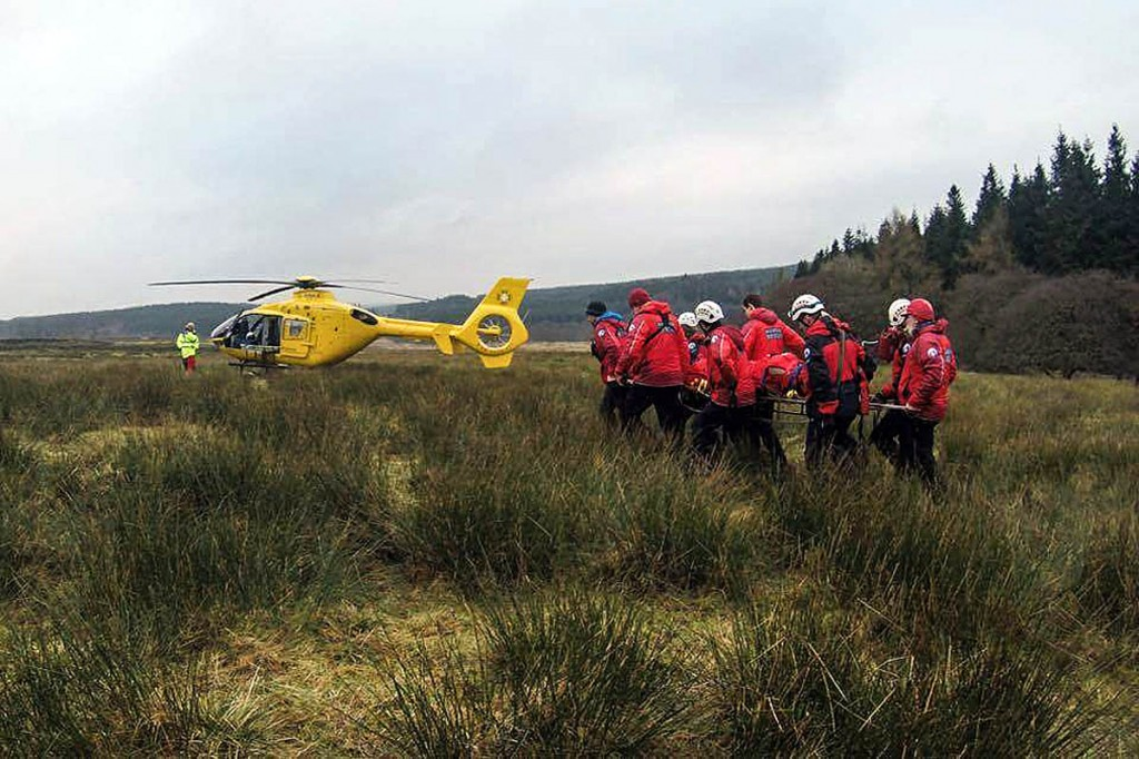 The injured mountain biker is stretchered to the air ambulance by rescuers. Photo: Bowland Pennine MRT
