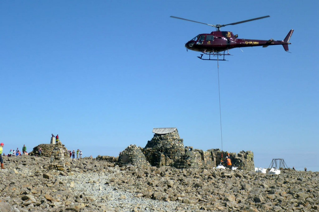 A helicopter lifts materials on to the summit during the restoration work. Photo: John Muir Trust