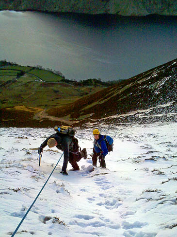 The stranded paraglider is lowered down snow slopes in the Red Gill area of Grasmoor above Crummock Water, with a team member cutting steps