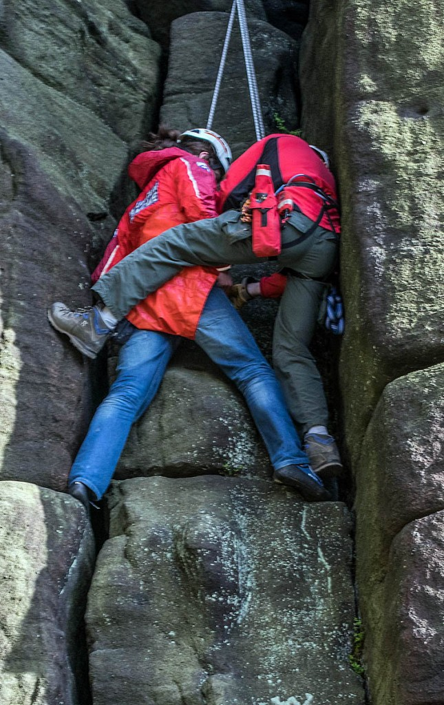 A rescuer with the climber at the scene. Photo: Calder Valley SRT
