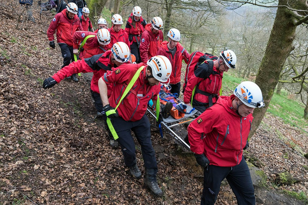 Members of the Calder Valley Search and Rescue Team stretcher the injured walker from the path in Crow Nest Wood, Hebden Bridge. Photo: Bob Smith/grough