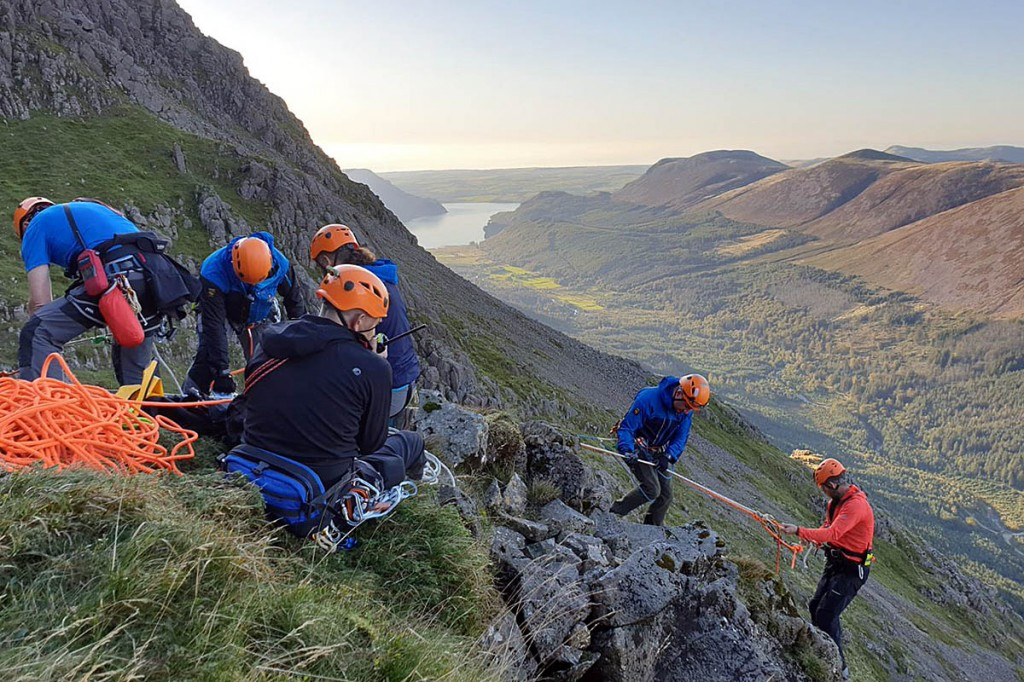A rescuer is lowered down the crag. Photo: Cockermouth MRT