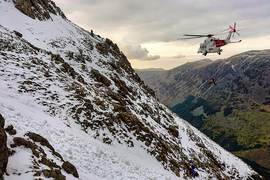 The Coastguard helicopter and rescuers at the scene, with avalanche debris in the foreground. Photo: Cockermouth MRT