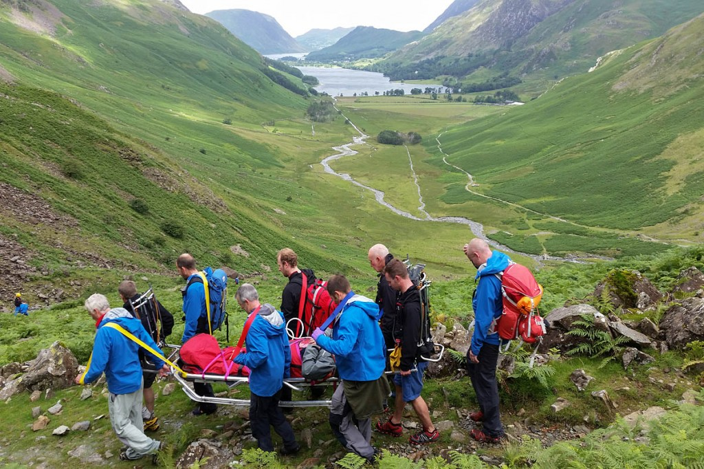 Rescuers stretcher the injured walker from the fell. Photo: Cockermouth MRT