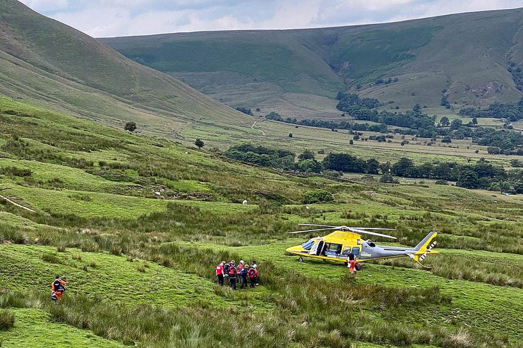 Team members stretcher the injured biker to the air ambulance on the slopes of Mam Tor. Photo: Edale MRT