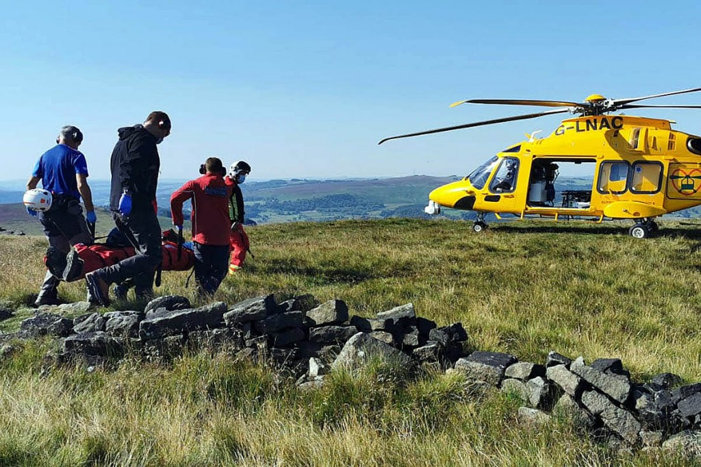 Team members strecher a casualty to an air ambulance. Photo: Edale MRT