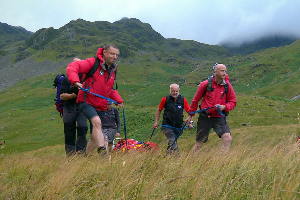 Patterdale team members stretcher a casualty from the fells in a scene from the series. Photo: Tern TV/More4