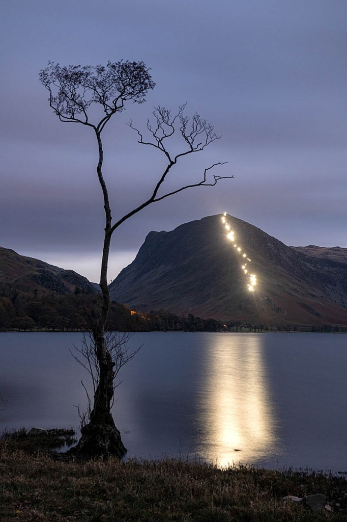 The lights of walkers' torches are reflected in Buttermere. Photo: Carmen Norman Photography