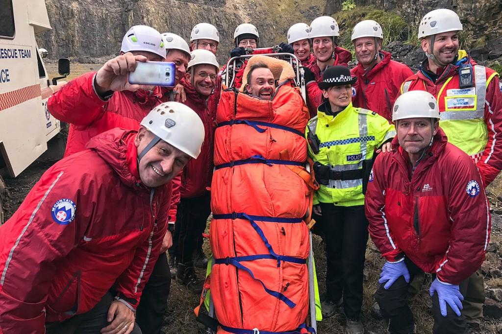Glossop team members with actor Daniel Brocklebank in their stretcher. Photo: Glossop MRT