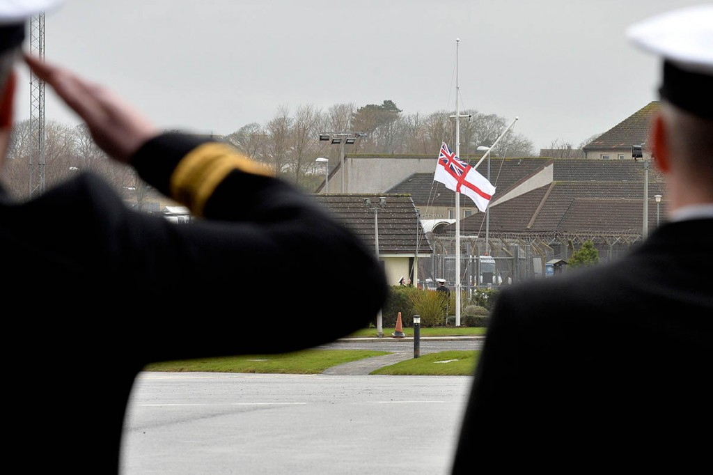 Members of HMS Gannet search and rescue flight salute the White Ensign for the final time
