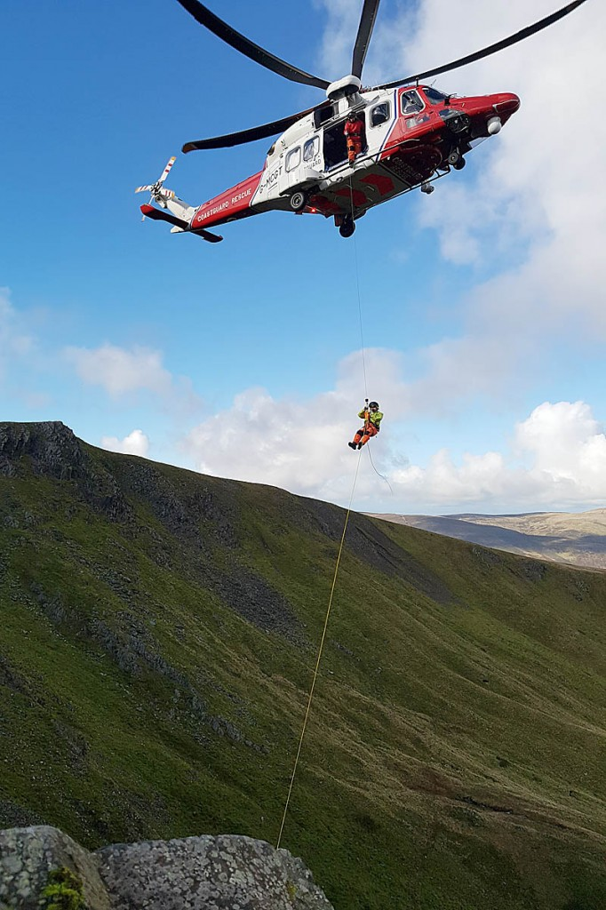 The Prestwick Coastguard helicopter and the crew's winchman at the rescue site. Photo: Keswick MRT