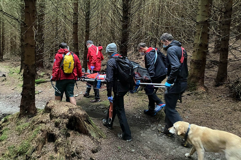 The team stretchers the injured mountain biker from the forest. Photo: Keswick MRT