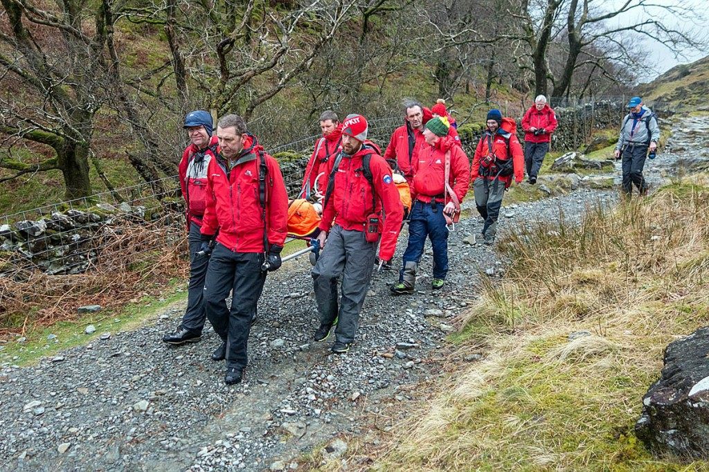 Team members stretcher the second injured walker from the fell. Photo: Keswick MRT