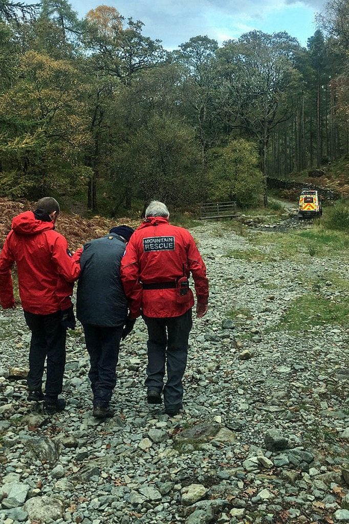 Rescuers help the injured walker to a team Land Rover. Photo: Keswick MRT