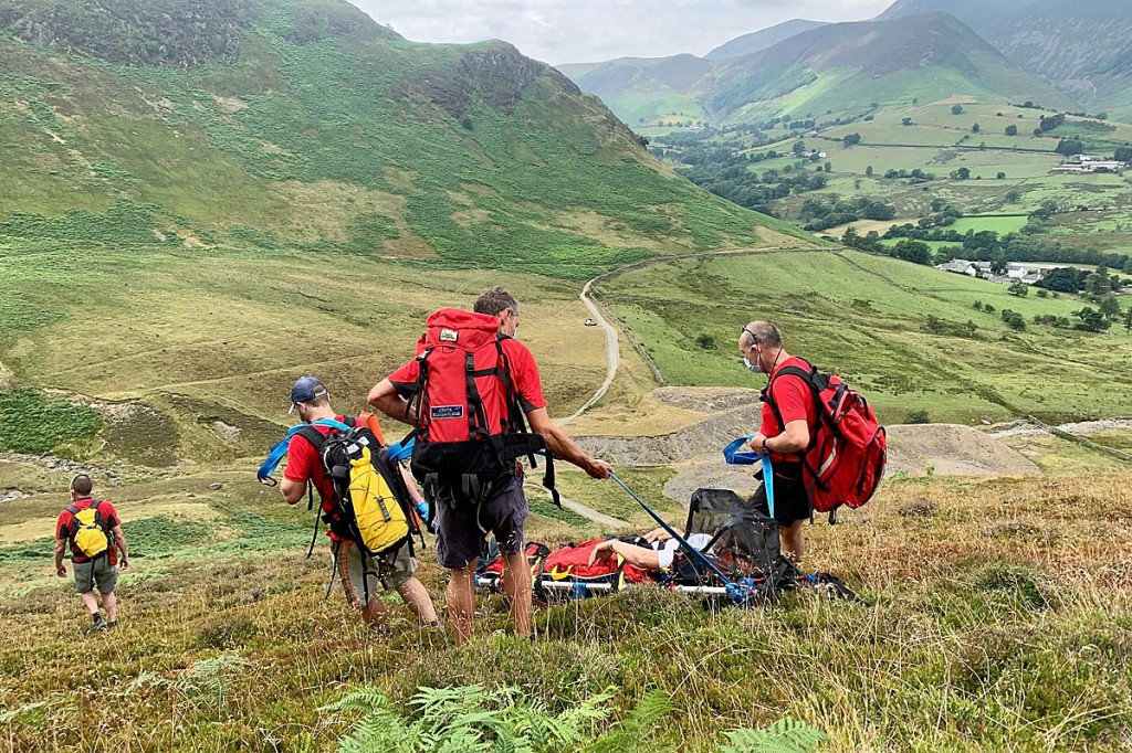 Rescuers stretcher the injured woman from the fell. Photo: Keswick MRT