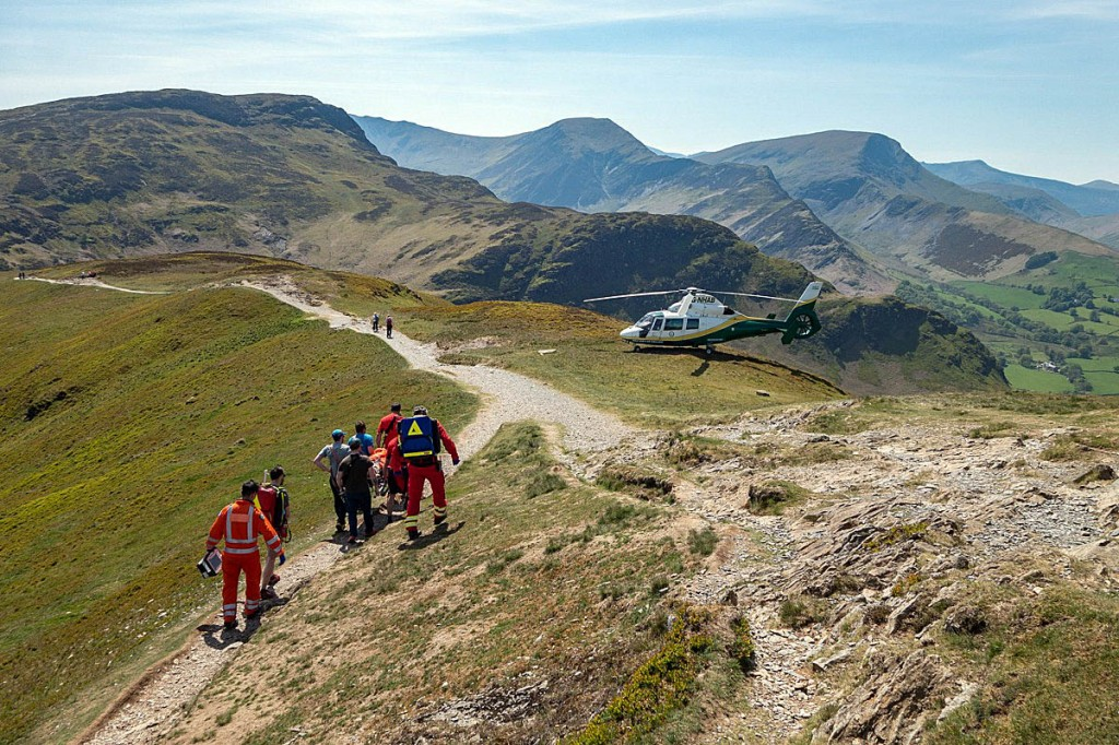 Rescuers stretcher the man to the air ambulance, which landed on the ridge. Photo: Keswick MRT