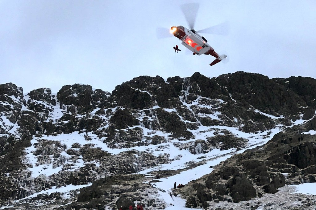 The Coastguard helicopter winches the injured climber from Great End. Photo: Keswick MRT