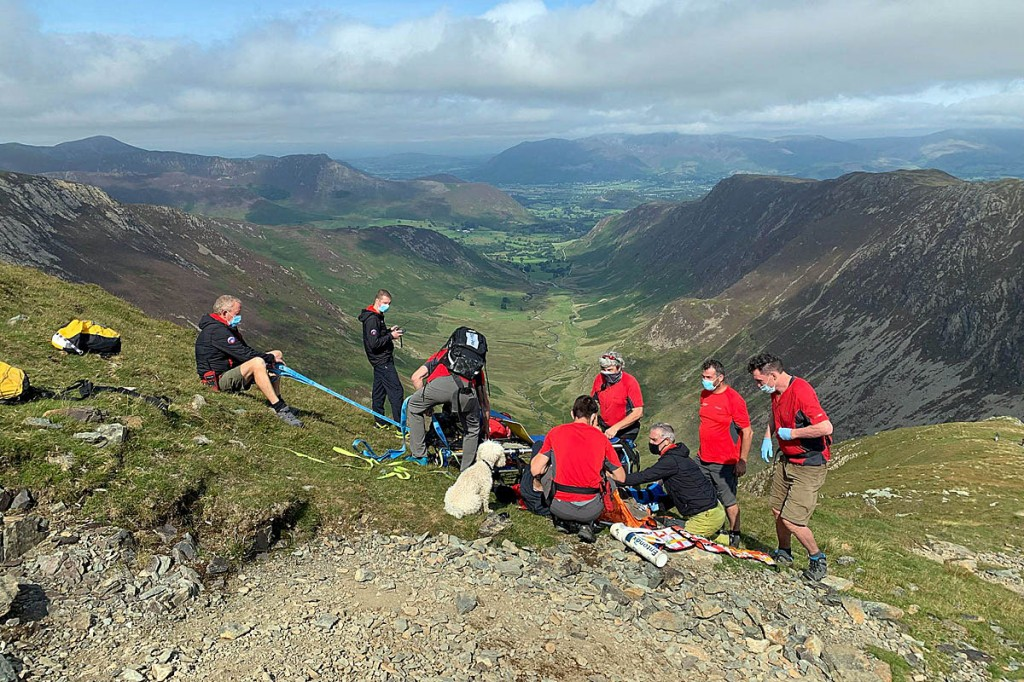 The injured walker's dog keeps a close watch as rescuers treat the man on Dale Head. Photo: Keswick MRT