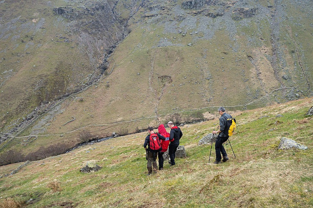 Rescuers aid the walker as she descends Eagle Crag. Photo: Keswick MRT