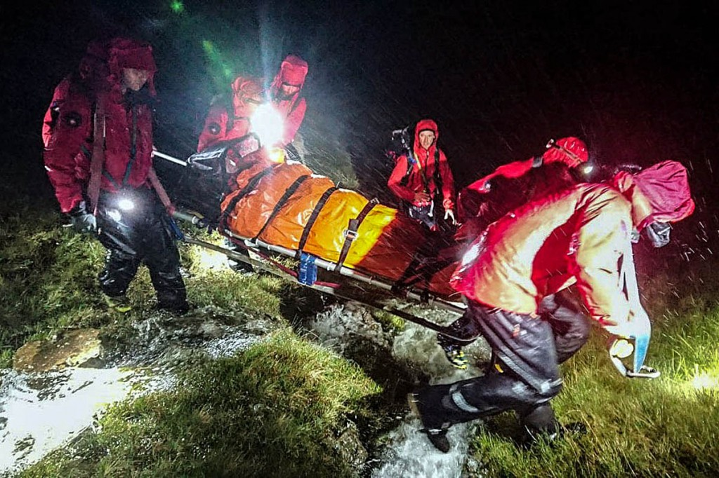 Rescuers stretcher the walker from the fell. Photo: Keswick MRT