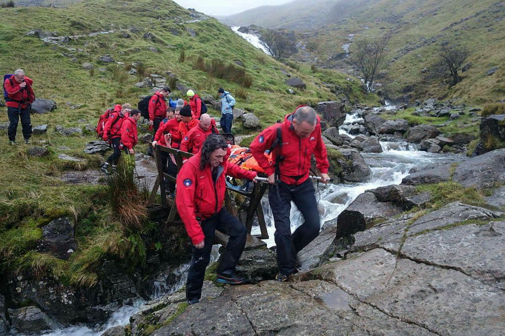 Rescuers stretcher the woman down Grains Gill after her fall. Photo: Keswick MRT