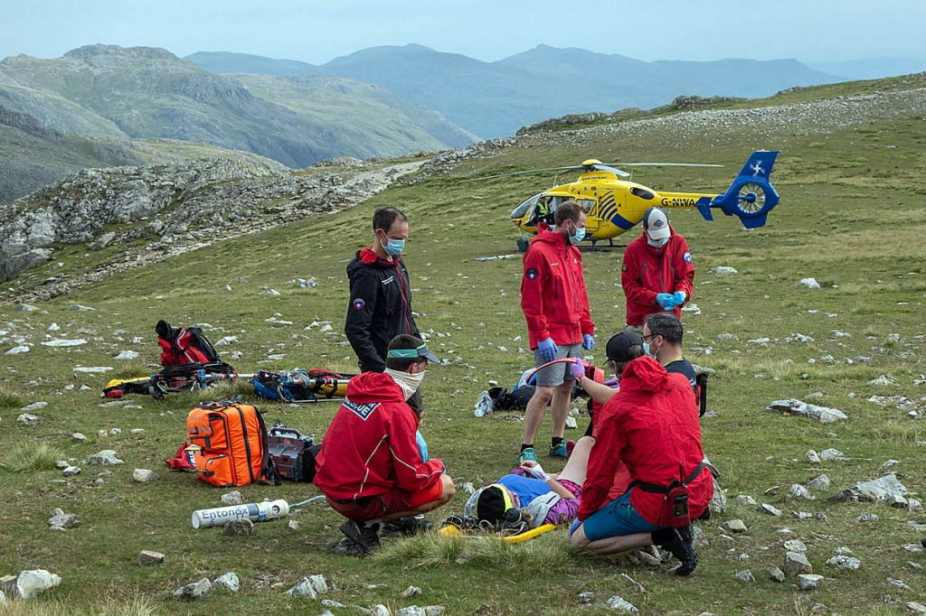 Rescuers tend to the injured runner, with the air ambulance in the distance. Photo: Keswick MRT