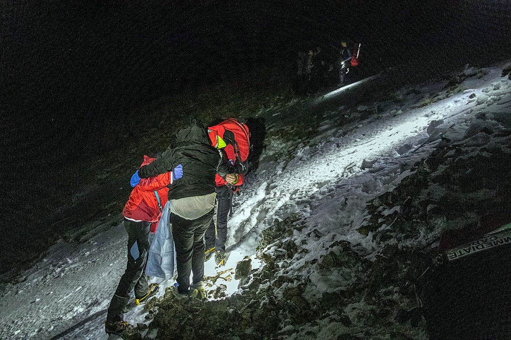 Rescuers support one of the group across the slope. Photo: Keswick MRT