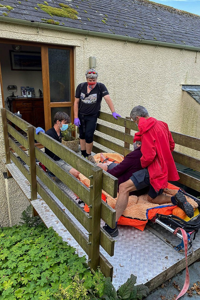 Rescuers with the injured woman at her holiday cottage. Photo: Keswick MRT