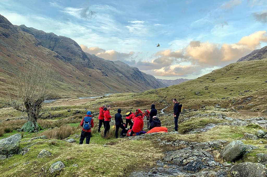 Rescuers with the injured man in Langstrath as the air ambulance approaches. Photo: Keswick MRT