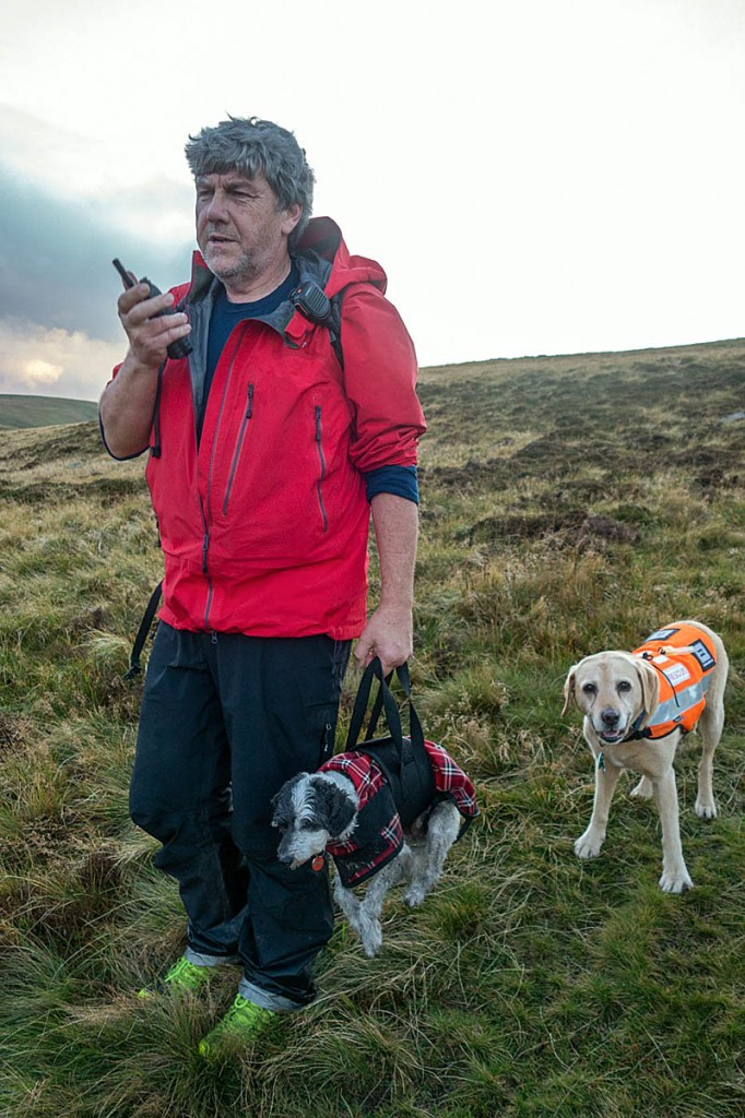 A team member demonstrates the doggy handbag, with a rescue dog keeping a watchful eye. Photo: Keswick MRT