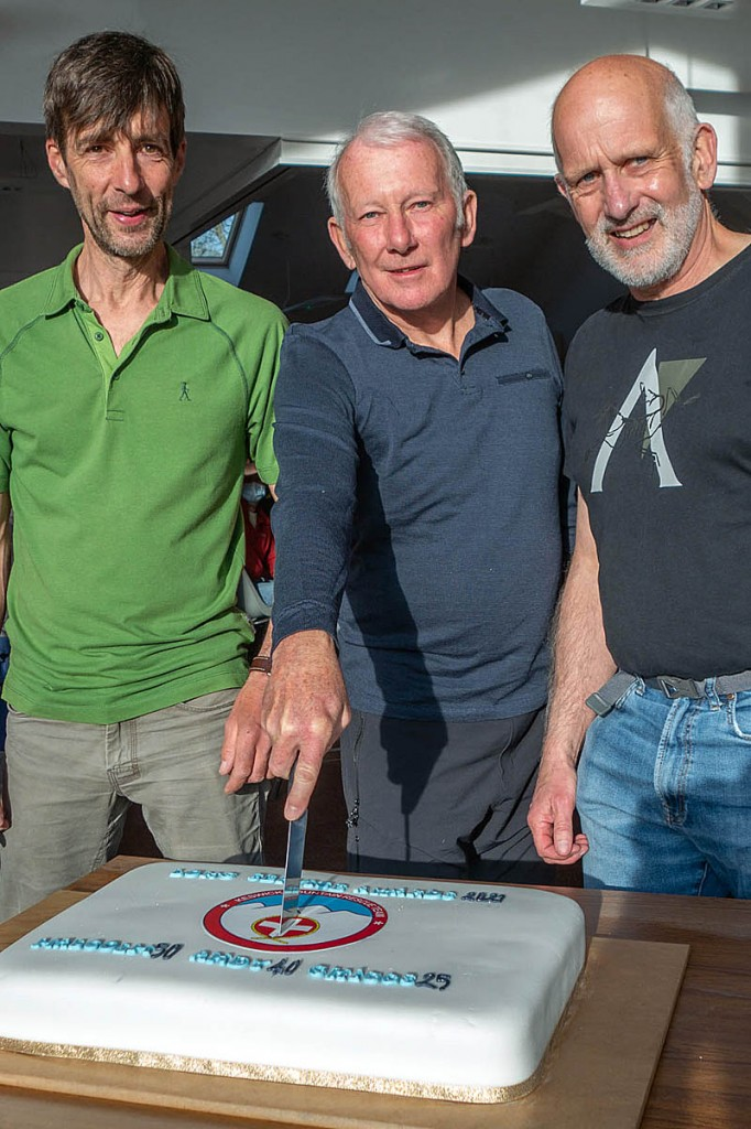 Malcolm Miller, Andy Jones and Chris Higgins with the cake. Dr Hooper was unable to attend the event. Photo: Keswick MRT