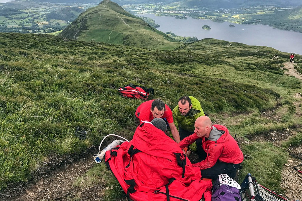 Team members tend to the injured walker on the fell. Photo: Keswick MRT