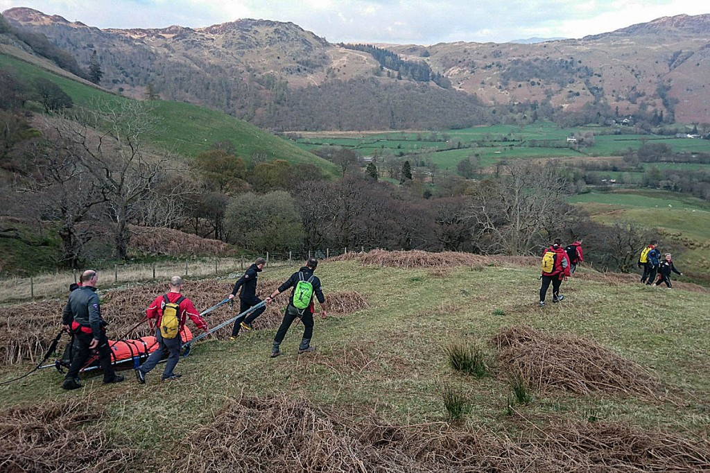 Rescuers stretcher the youth from the fell. Photo: Keswick MRT