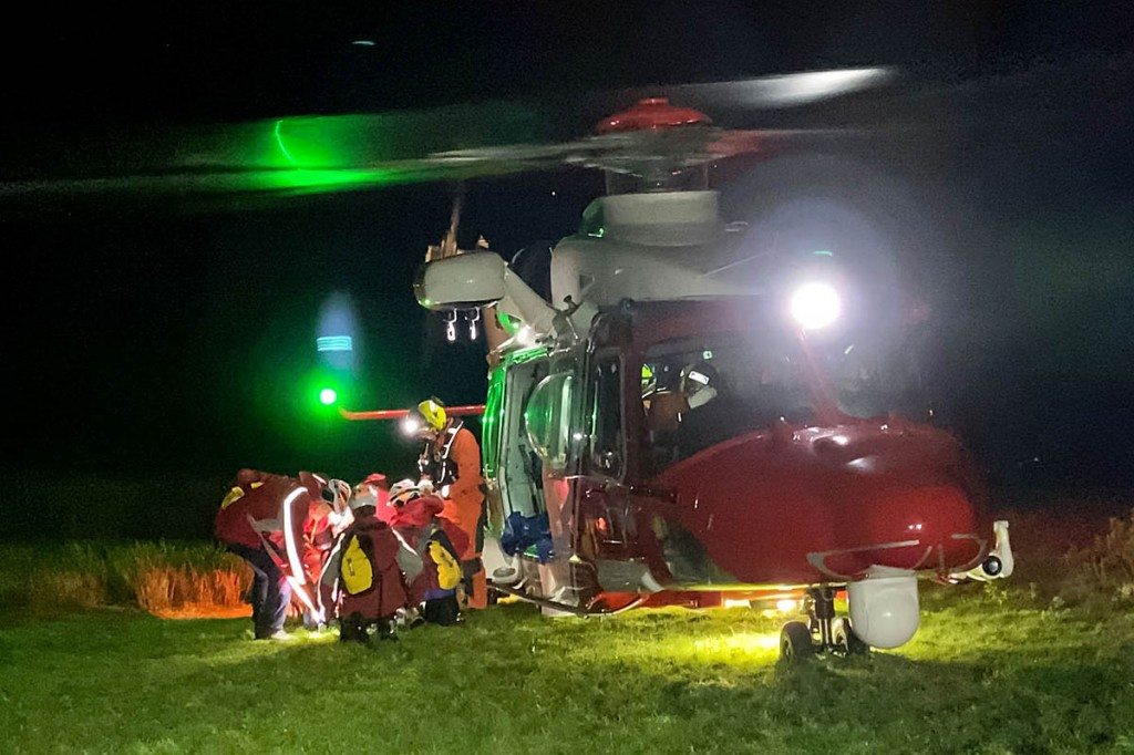 Rescuers with the Coastguard helicopter and the injured man. Photo: Keswick MRT