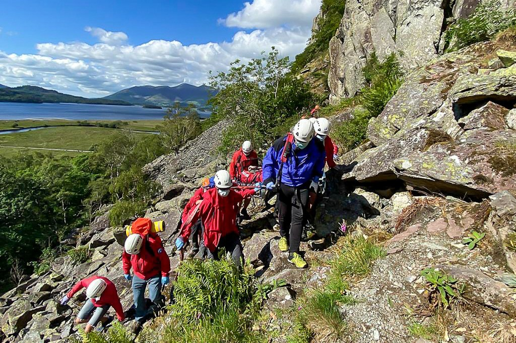 Rescuers stretcher the climber from the crag. Photo: Keswick MRT