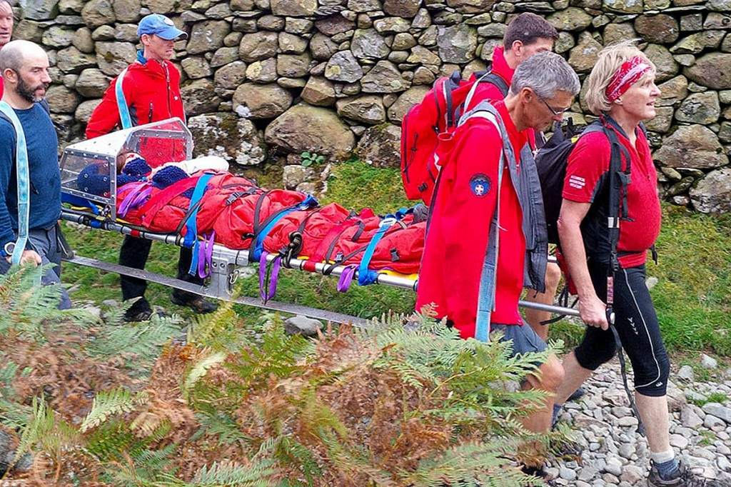 Team members stretcher one of the walkers from the fell. Photo: Keswick MRT