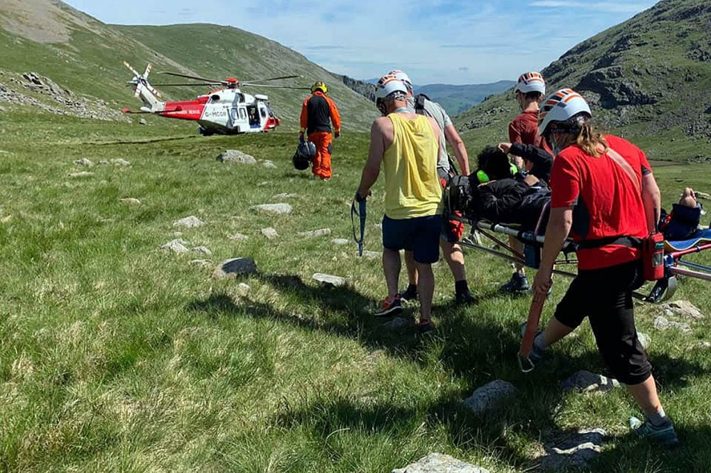 Rescuers stretcher the injured walker to the waiting helicopter. Photo: Keswick MRT