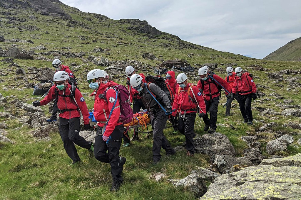 Wasdale Mountain Rescue Teams in PPE during a stretcher carry on a hot, humid day