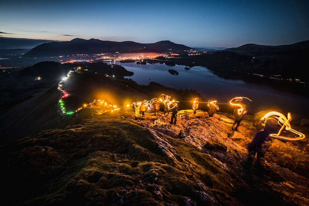 Walkers light up Cat Bells, with Derwent Water and Keswick in the distance. Photo: Harry Baker Photography