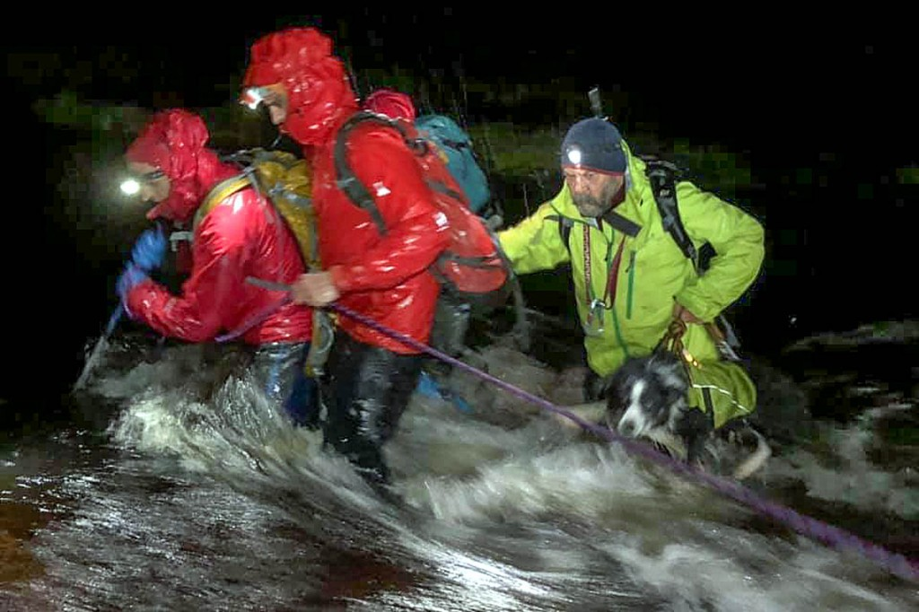 Team members and search dog Megaidh cross a swollen river during the search. Photo: Lochaber MRT