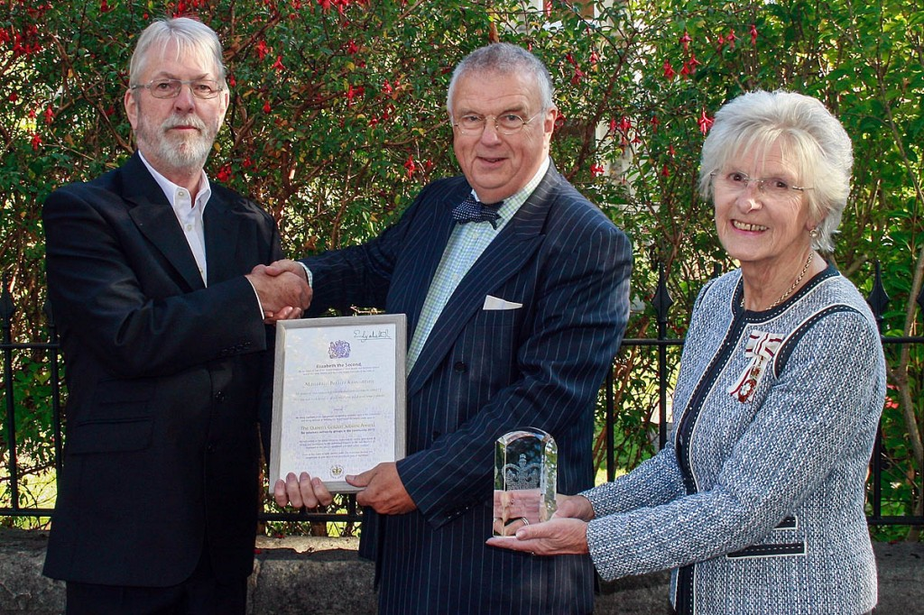 Simon Birch, left, receives the Queen's Award for Voluntary Service from Mary Prior and Dr Timothy Chambers in a ceremony in Bristol