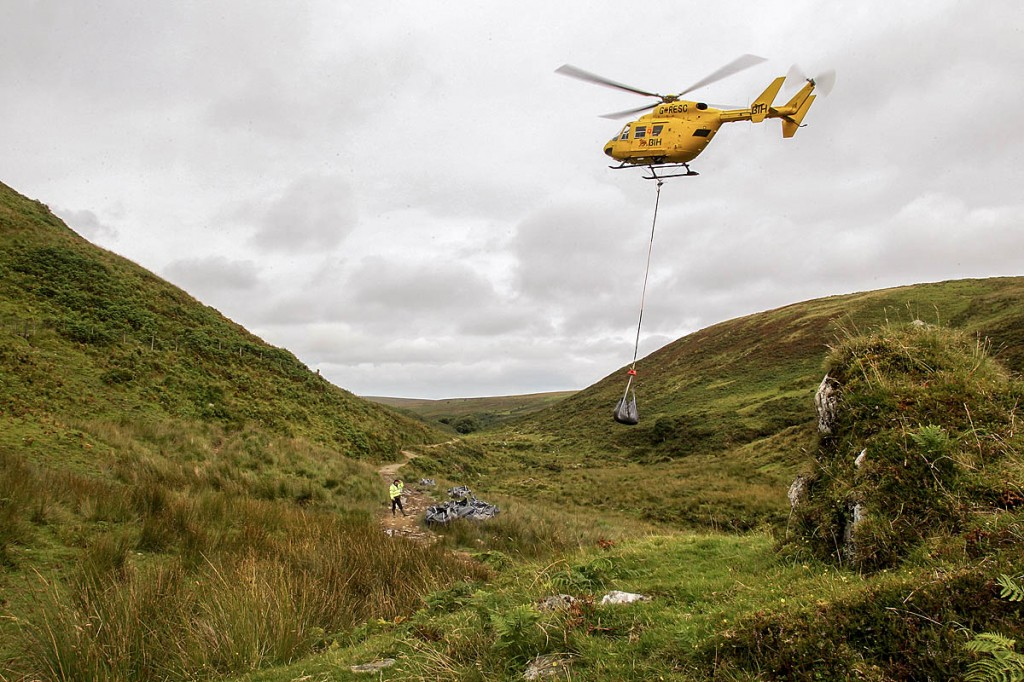 A helicopter lifts stone to the site on Exmoor