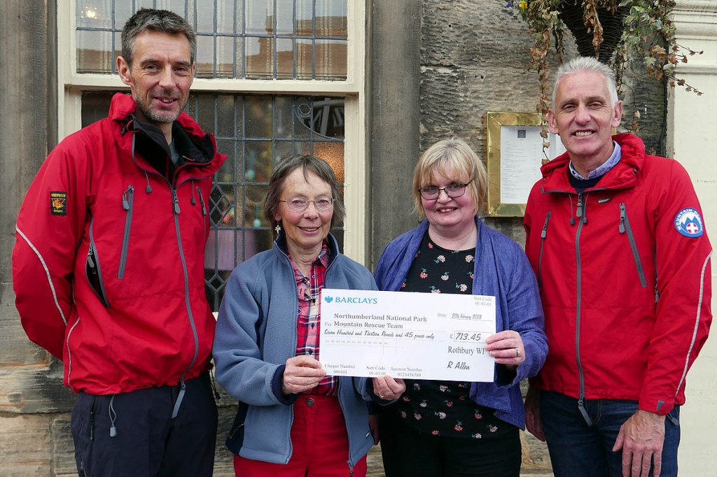 Iain Nixon, left, and fellow team member Andrew Miller received the cheque from Ros Allen, second from left, and Rothbury Parish Council chair Caroline Dawson. Photo: Northumberland NPMRT
